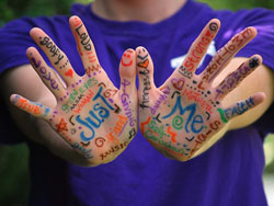 boy holding up hands with decorative writing